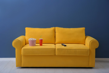 Comfortable sofa with popcorn, drink and remote control in home cinema. Watching movie