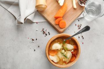 Tasty broth with dumplings on table