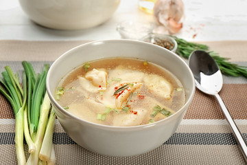 Bowl with tasty broth and dumplings on table