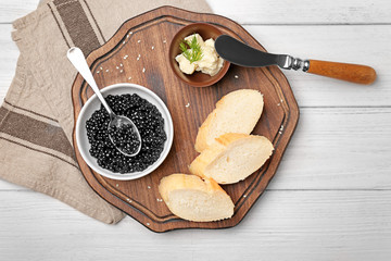 Black caviar served with bread and butter on wooden board