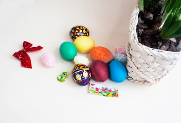 Easter eggs, a glass frog,bow, bud of a hyacinth, a wicker basket on a light paper background.