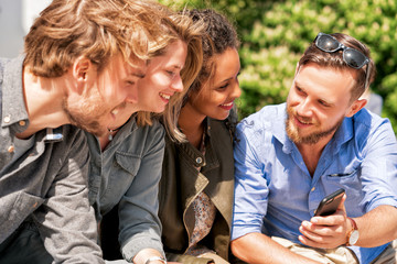 Group of multiracial friends have fun while looking photos Vilnius