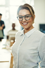 Confident young businesswoman wearing glasses standing in an office smiling