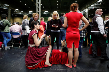Women wait to enter the ring with their Yorkshire Terriers during the third day of the Crufts Dog Show in Birmingham
