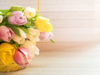 Bouquet of colorful tulips in a yellow wicker basket
