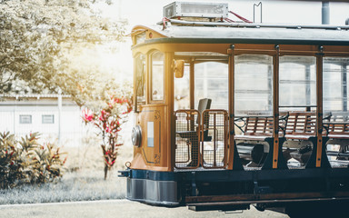 Side shot of empty yellow glossy excursion tram waiting at tramway station: opened interior with wooden windows and seats inside, single headlight, sunny day; Rio de Janeiro, Brazil