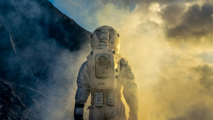 Courageous Astronaut in the Space Suit Explores Mysterious Alien Planet Covered in Mist. Adventure. Space Travel, Habitable World and Colonization Concept.