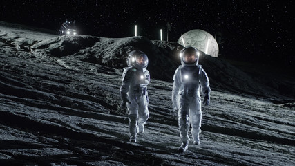 Two Astronauts in Space Suits Walk on the Alien Planet Looking at the Sky. In the Background Base with Geodesic Dome. Other Worlds Colonization and Space Travel Concept.