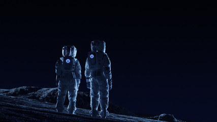 Two Astronauts in Space Suits Stand on the Alien Planets Observing Extraterrestrial Terrain. Space Travel and Extraterrestrial Colonization Concept.