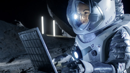 Female Astronaut Wearing Space Suit Works on a Laptop, Exploring Newly Discovered Planet, Communicating with the Earth. In the Background Her Space Habitat. Colonization Concept.