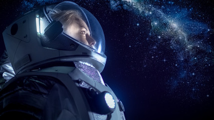 Portrait of the Beautiful Female Astronaut on the Alien Planet Looking at the Milky Way Galaxy. Space Travel, Exploration and Solar System Colonization Concept.