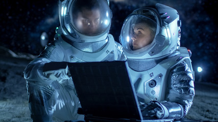 Two Astronauts Wearing Space Suits Work on a Laptop, Exploring Newly Discovered Planet, Communicating with the Earth. Space Travel, Exploration and Colonization Concept.