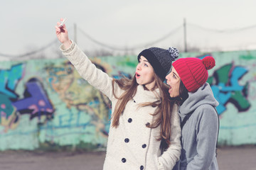 Two happy millennial teenage girl in coats and hats taking a selfie on smart phone