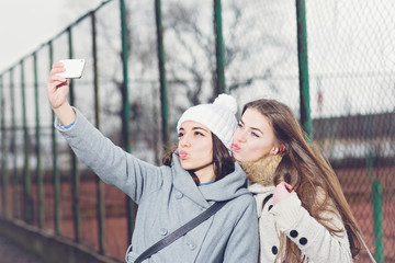 Two cheerful teenage girls taking a selfie in school yard in winter. Female friends taking a photo outdoors.