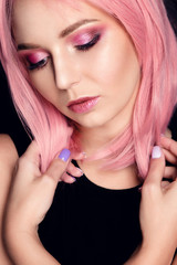Model with pink hair and professional make-up. Young beautiful girl, close-up portrait