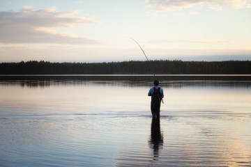 Man fishing on a beautiful quiet lake