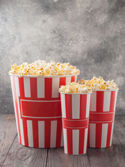 Popcorn in three striped buckets (red and white boxes) isolated on grey wooden table (background). Selective focus. Copy space. Nobody.