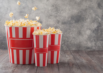 Popcorn in a three striped buckets (red and white boxes) isolated on grey wooden table (background). Flying pop corn. Selective focus. Copy space. Nobody.