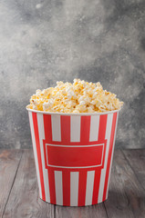Popcorn in a striped bucket (red and white box) isolated on grey wooden table (background). Selective focus. Copy space. Nobody. Front view.