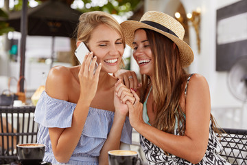 Portrait of of beautiful female in summer blouse, speaks via cell phone, happy to hear someone, keeps hands with girlfriend, have fun together in coffee shop, drink aromatic cappuccino, laugh joyfully