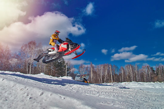 Sports race snowmobiles. Snowmobile in  high jump above track. Sportsman on snowmobile. Winter competition, sunny day, blue sky. Copy space.