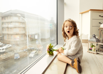 .A little girl with a bouquet of flowers on her mother's day sits at the window and laughs at her mother, gives a bouquet of flowers.