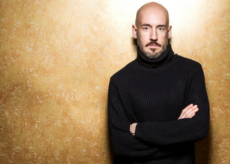 Fashion Portrait of 40-year-old man standing over light gold background in a black sweater. Close up. Classic style. Bald shaved head. Copy-space. Studio shot