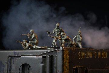 Smoke billows behind toy soldiers on ammo can