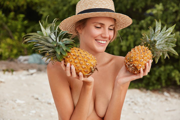 Beautiful young female model poses half nude against sandy beach background, keeps two exotic pineapples, being in good mood. Cheerful woman prepares for summer party. Vacation and rest concept