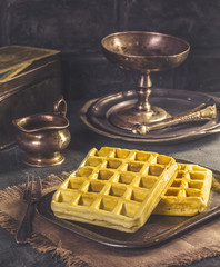 Fresh Belgian waffles on vintage tray in dark tones