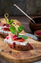 Brie, prosciutto and mint on bread appetizer snack