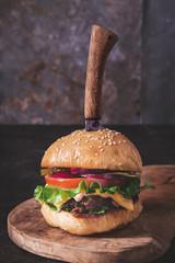 Homemade hamburger with knife  on dark background closeup