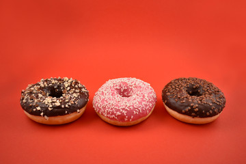 Chocolate donuts stock images. Donut on a red background. Three donuts isolated on a red background. Chocolate and strawberry donuts