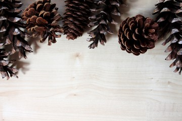 Pine cones top border on light wood background. Copy space.