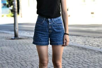 Młoda dziewczyna w dżinsowych spodenkach na ulicy.