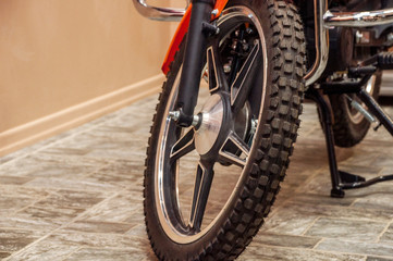 Front wheel of a new clean shiny motorcycle in a room on the floor in the form of a cobblestone pavement