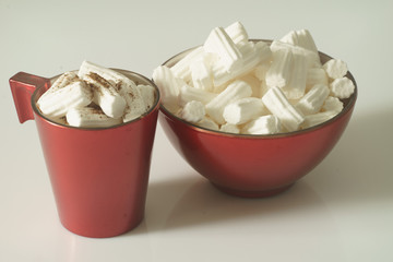 A Cup of coffee or hot chocolate with marshmallows and a red plate on a white background. Close up. Christmas photo.