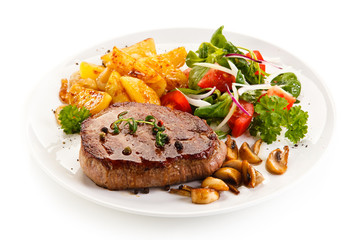 Grilled beef steak with baked potatoes and vegetables