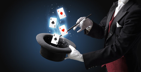 Magician making trick with wand and playing cards