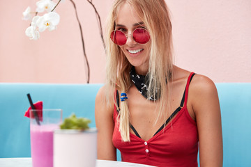 Photo of cheerful blonde woman wears fashionable red shades, bandana on neck and pink tank top, enjoys good rest in cozy cafe with calm atmosphere, drinks exotic smoothie or cocktail with pleasure