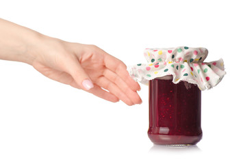 Raspberry jam in a jar in hand