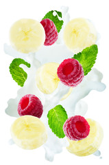 Flying raspberry and banana with mint leaves and a spray of milk