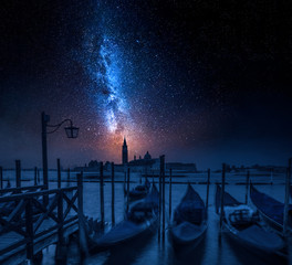Blue gondolas in Venice at night with stars