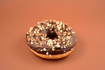 Chocolate donut with nuts stock images. Donut on a brown background. Donut with chocolate frosting and nuts