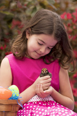 Little girl with easter basket playing with baby chick.
