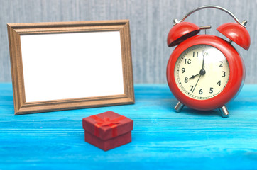 Present gift box and empty photo frame with copy space and red retro alarm clock on wooden table background.