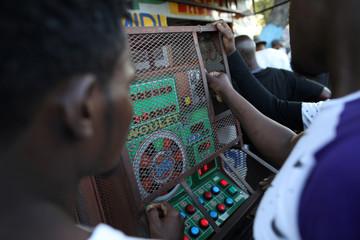 Men play with a slot machine along a street of Port-au-Prince