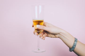Woman hand with glass of champagne isolated on a pink background