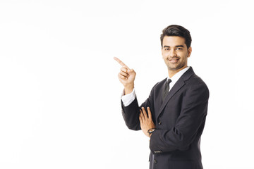 Portrait of a smiling, successful businessman in black suit and tie pointing up isolated on white background