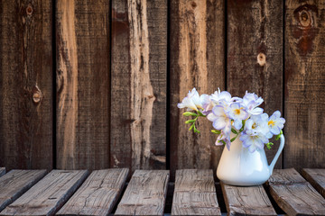 A bunch of freesia flowers in a white ceramic pitcher on a rustic wooden plank table.